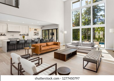 Beautiful Living Room and Kitchen in New Modern Luxury Home. Features Wall of Windows, Floor to Ceiling Fireplace Surround