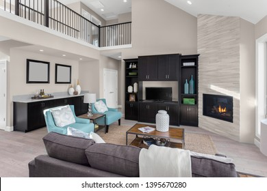 Beautiful living room in new home with fireplace, built-ins, hardwood floors, and view of second story landing area