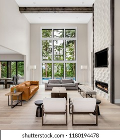Beautiful living room in new luxury home wall of windows, floor to ceiling fireplace surround, hardwood floors, and exterior view of pool and trees