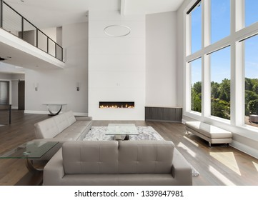 Beautiful living room in new luxury home with large bank of windows showing exterior view.