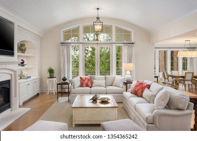Beautiful living room in new luxury home with French Doors, Fireplace, Built-Ins, and View of Dining Room