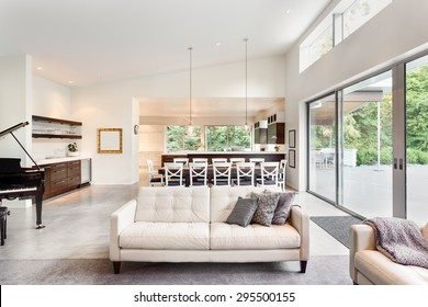Beautiful living room in new luxury home with couch, piano, sliding glass doors leading out to backyard patio, huge dining room table, pendant lights, vaulted ceilings, wet bar, and kitchen