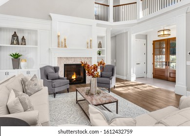 Beautiful living room in new traditional style luxury home. Features vaulted ceilings, fireplace with roaring fire, and elegant furnishings. Shows foyer front door.