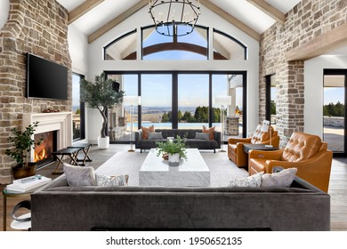 Beautiful living room in new traditional  luxury home. Features stone accents, vaulted ceilings, fireplace with roaring fire, and gorgeous exterior view of infinity pool and valley. - Shutterstock ID 1950652135