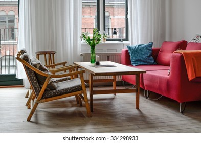 A beautiful living room with red sofa, wooden tables and flowers