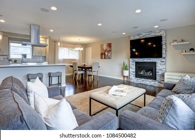 Beautiful living room with stone fireplace. Open floor plan features kitchen and dining space.