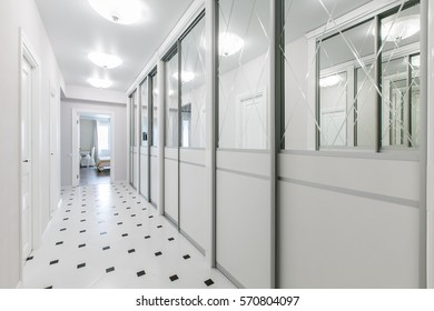 Beautiful lobby in a luxurious apartment. Black and white tile on the floor. White rolling door wardrobe with mirrors.