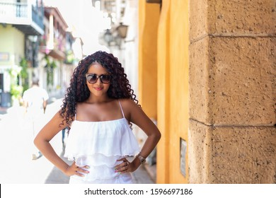 Beautiful local Colombian woman in white dress in the walled city of Spanish colonial architecture - Cartagena, Colombia