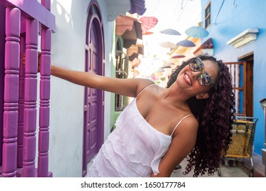 Beautiful local Colombian woman in white dress in the walled city of Cartagena, Colombia