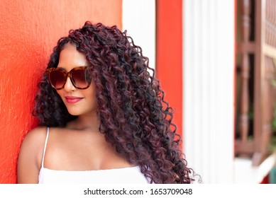 Beautiful local Colombian woman in white dress in front of red wall in the colorful city of Cartagena, Colombia