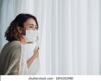 Beautiful lonely Asian woman wearing medical face mask looking out the window with copy space, stay at home, self quarantine. Stay safe concept, prevention COVID-19 or Coronavirus pandemic situation.