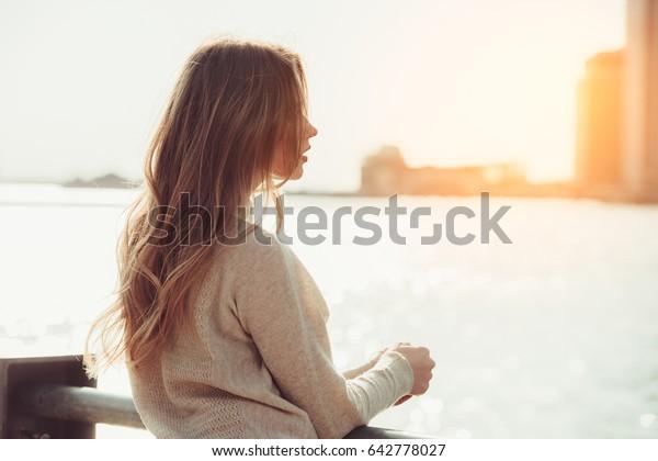 Schönes einsames Mädchen, das träumt und denkt, während es auf das Datum wartet in der Stadt Ozean Pier bei Sonnenuntergang.