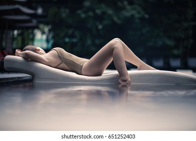 Beautiful lonely girl lies on a lounger in a swimsuit in the pool in tropics of Malaysia. Woman in the pool water