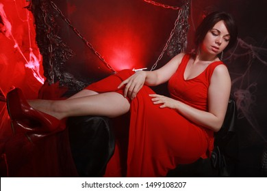 beautiful lonely girl in long red dress on the halloween throne ready for scary party