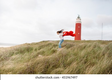 Beautiful lonely girl wrapped up in a blanket walking on a beach with a red lighthouse on Texel island, Holland, Netherlands
