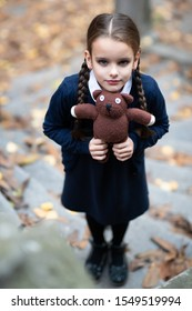Beautiful lonely little girl with with pigtails, dressed in dark blue standing near mystic abandoned building with gothic stairs and holding handmade bear toy. Halloween horror. Loneliness, depression