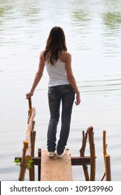 Beautiful lonely teenage girl standing on the edge of the river dock.