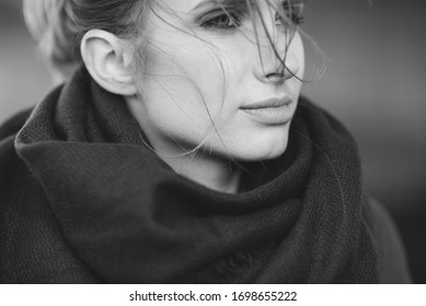 Beautiful lonely woman in a coat and scarf with her hair developing in the wind under a bridge on a cold gray day. The concept of loneliness. Black and white art photo. Soft selective focus.