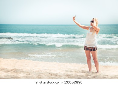 Beautiful lonely woman traveler on beach taking picture selfie on phone during beach travel holidays vacation for social media concept traveling lifestyle vintage style