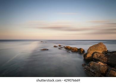 Beautiful long exposure landscape of sea over rocks at sunset