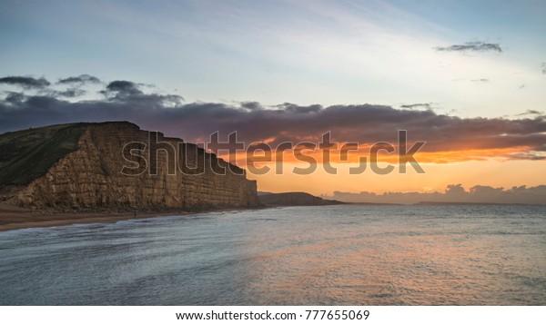 Beautiful long exposure sunrise landscape image of West Bay in Dorset England
