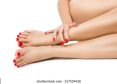 Beautiful long female bare sexy legs with red pedicure, female foots with red pedicure and hands with red manicure close up, isolated