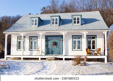 Beautiful long french-style ancestral white clapboard house with blue trimmed windows, blue door and metal roof seen during a sunny winter afternoon, Sillery area, Quebec City, Quebec, Canada