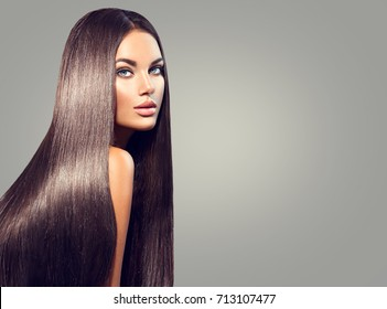Beautiful long Hair. Beauty woman with luxurious straight black hair on dark background. Beautiful brunette Model girl with Healthy Hair. Lady with long smooth shiny straight hair. Hairstyle, cure