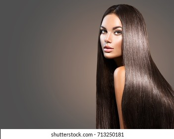Beautiful long Hair. Beauty woman with luxurious straight brown hair on dark background. Beautiful brunette Model with Healthy Hair. Lady with long smooth shiny straight hair. Hairstyle, cure
