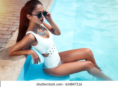 beautiful long hair female model posing by the pool, outdoor portrait.Beautiful sexy young girl with perfect slim figure with long wet hair in bikini and sunglasses sitting  in swimming  pool