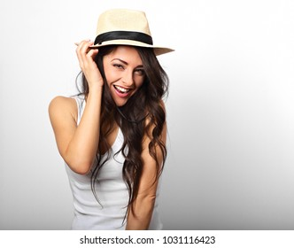 Beautiful long hair laughing woman in white top and straw hat looking happy on white background