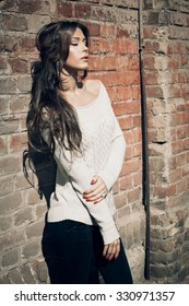 beautiful long hair young woman wearing white sweater lean on red brick wall, outdoor shot sunny autumn day