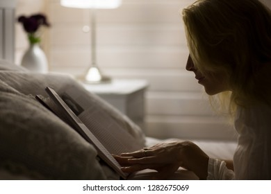 Beautiful long haired blonde woman lays on bed, and read book in dark room at night.