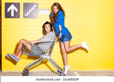 beautiful long haired girl in jeans mini skirt rides a boy in hat on shopping trolley in front of yellow brick wall
