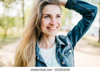 Beautiful long haired girl with postive emotional face outdoor art portrait. Cheerful smiling happy young woman at nature. Amazing stylish female with blue eyes posing outside. Laughing mood person