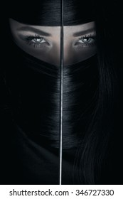 Beautiful long haired ninja woman holds katana sword in front of her face. La femme fatale