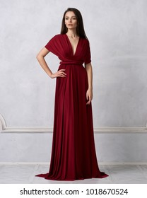 Beautiful long haired young woman dressed in stylish cherry red bandeau maxi dress posing against white wall on background. Elegant brunette female model demonstrating evening outfit in studio.