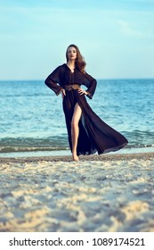 Beautiful long legged woman with perfect body wearing trendy chiffon oriental black chiffon beach cover up stepping lightly on the sand, her hair and the train of her gown flying in the wind