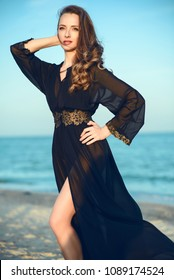 Beautiful long legged woman with perfect body wearing trendy chiffon oriental black chiffon beach cover up standing on the beach, her hair and the train of her gown flying in the wind