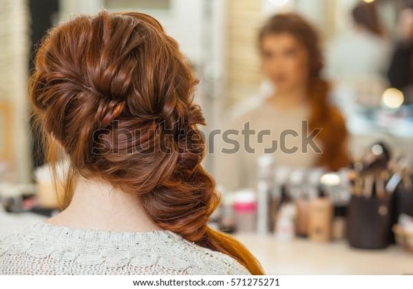 Mooi, met lang, roodharig harig meisje, kapper weeft een Franse vlecht, in een schoonheidssalon. Professionele haarverzorging en het creëren van kapsels.