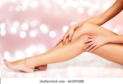 Beautiful long woman's legs and hands with smooth and soft skin on an abstract background with blurred lights