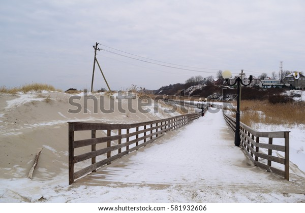 Beautiful long wooden promenade on the nature on the lake in winter