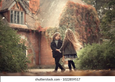Beautiful long-haired blonde girl is dancing with a cute boy in autumn old park near the ivy-covered ancient mansion in Pushkin, Russia. Image with selective focus and toning.