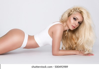beautiful long-haired blonde slim blonde with perfect face stands on a white background in underwear slimming and sensually looks into the lens