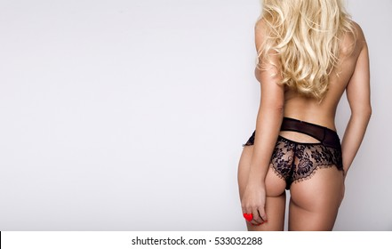 Beautiful long-haired blonde woman standing on a white background backs in sexy underwear, stockings, high heels and lacy panties sticking out buttocks, has perfect body