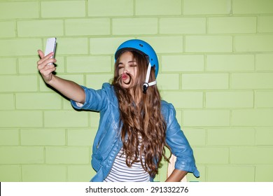 beautiful long-haired brunette girl in blue helmet taking a selfie self portrait of herself with mustache made of her ringlet curl hair at the camera on her smartphone digital camera near brick wall