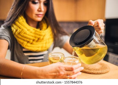 Beautiful long-haired brunette mistress hospitably treats guests with tea in a modern kitchen