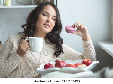 Beautiful long-haired brunette sitting on the sofa with a cup of hot drink and macaroon.