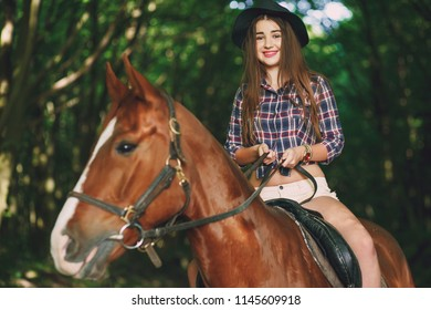 Beautiful long-haired girl in a green forest with a beautiful horse