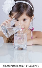beautiful long-haired girl pours water from a beaker to another